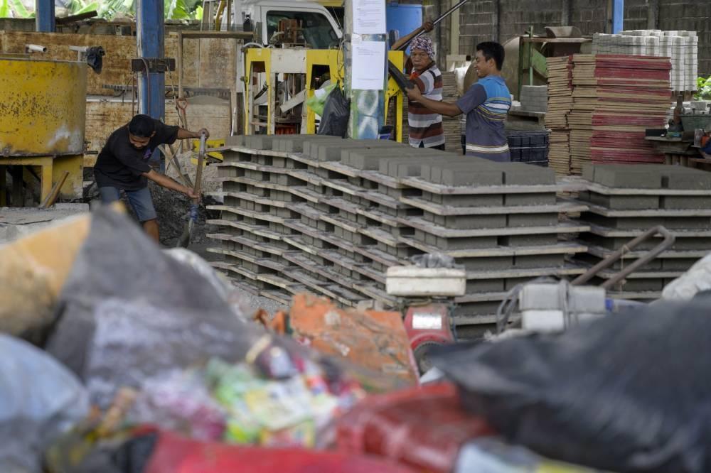 Foto ini diambil pada 7 April 2021, menunjukkan para pekerja menggunakan peralatan pengepresan untuk membentuk batu bata di sebuah pabrik pembuatan batu bata di Jakarta.  Foto oleh AFP