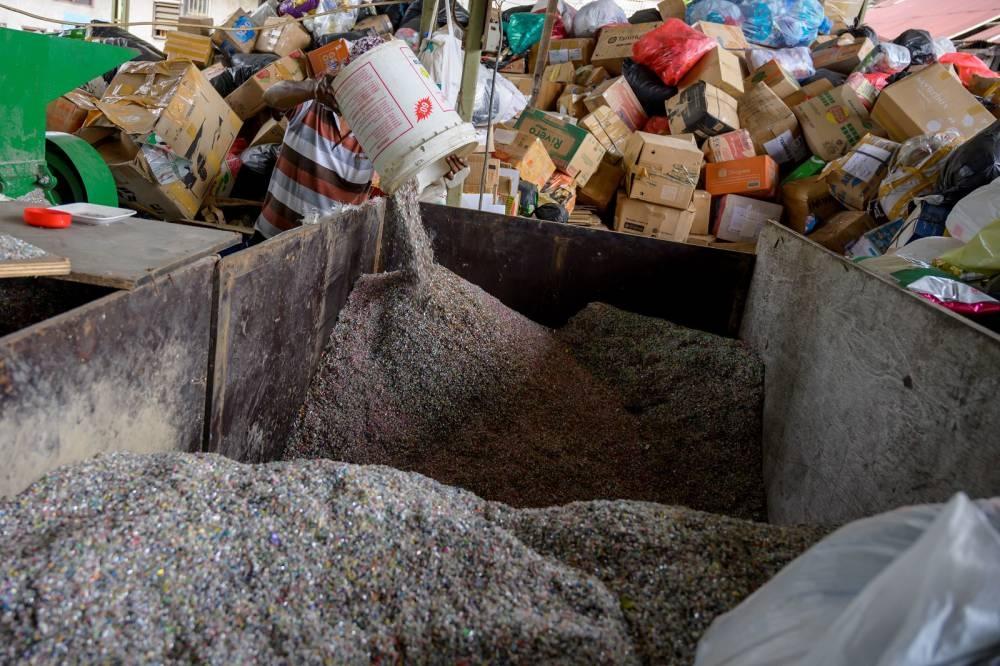 Pekerja menuangkan keripik dari sampah plastik daur ulang di sebuah pabrik pembuatan batu bata di Jakarta.  Foto oleh AFP