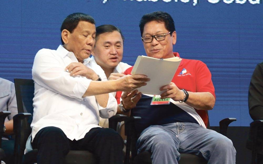Labor Secretary Silvestre Bello 3rd (right) confers with President Rodrigo Duterte and Senator Christopher Lawrence Go during an event in Cebu. PHOTO COURTESY OF PRESIDENTIAL COMMUNICATIONS OPERATIONS OFFICE