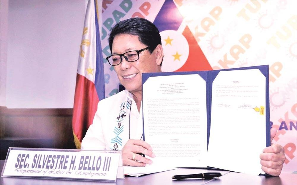 Labor Secretary Silvestre Bello 3rd shows the signed copy of the new Memorandum of Understanding (MoU) on cooperation in the deployment of private staff, stating among others that household staff will receive additional benefits and protection. PHOTOS COURTESY OF DOLE
