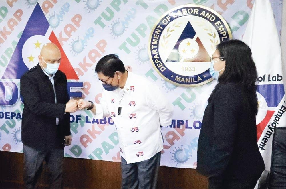 Labor Secretary Bello and Philippine Ambassador to Israel Macairog Alberto (left) greet each other with a fist bump while Vice Consul Judy Razon (right) looks on during a courtesy visit on May 12, at the Department of Labor and Employment Central Office in Intramuros, Manila.