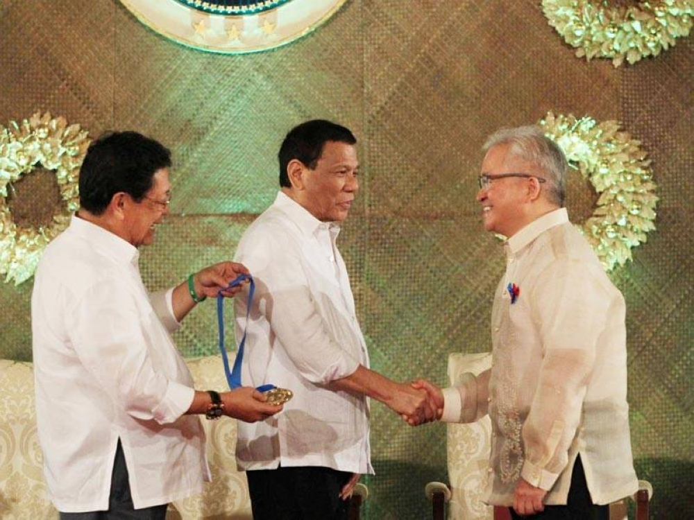 Sayas (extreme right) receiving the Presidential Award for Filipino Individuals and Organizations Overseas in December 2018