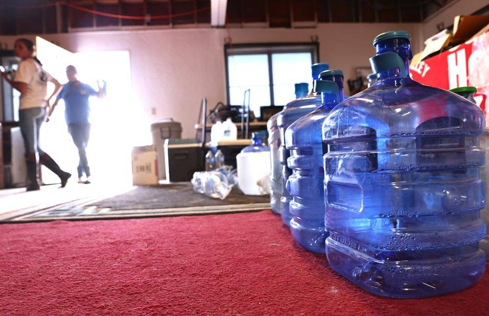 Volunteers stand near water bottles, now empty, which were donated by community members at Coachella Valley Horse Rescue, amid a water shortage at the rescue, on July 11, 2021 in Indio, California. The well that normally supplies running water to the rescue recently broke and they have been relying on water donations from the community and local fire department to keep their 18 horses alive amid a heat wave in California. 'Dangerously hot conditions' are hitting the Coachella Valley this weekend with possible highs of 115 to 120 degrees, according to the National Weather Service. An excessive heat warning was issued for much of California through Monday. Climate models almost unanimously predict that heat waves will become more intense and frequent as the planet continues to warm. AFP PHOTO