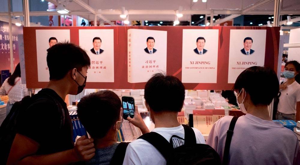 VITAL TRADE HUB Visitors take photos of a banner illustrating a book by Chinese President Xi Jinping at a booth at the annual Hong Kong Book Fair in Hong Kong on July 17, 2021. AFP PHOTO