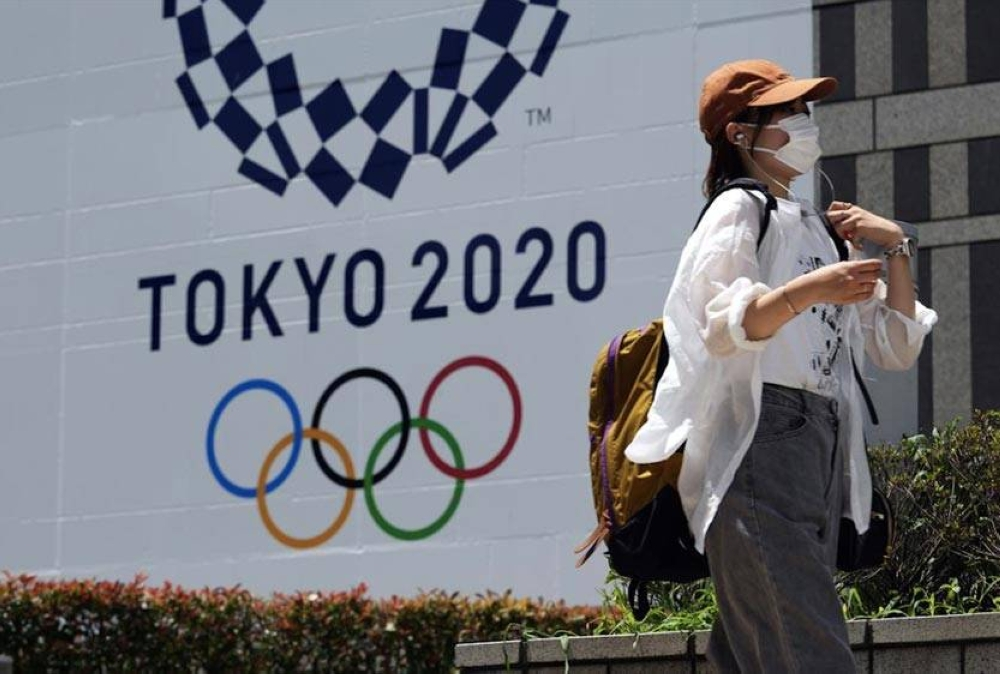 In this July 20, 2021 file photo, a woman wearing a protective mask walks in front of a Tokyo 2020 Summer Olympics display at the Tokyo Metropolitan government in Tokyo. AP PHOTO