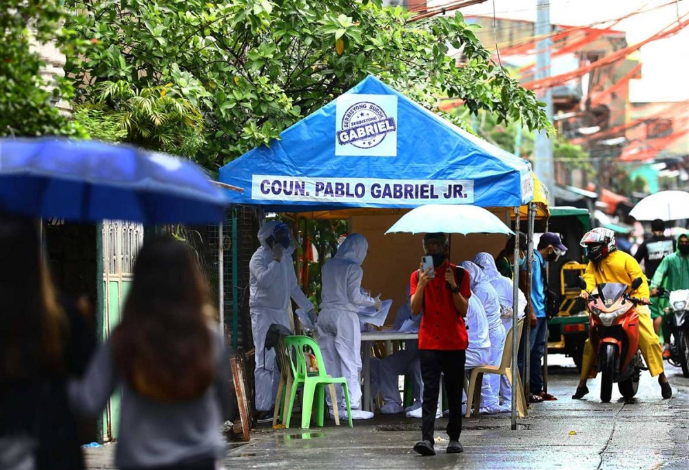 CONTAINING DELTA Health workers put up a workstation in Barangay San Dionisio Tramo 2, Parañaque City after two villages were placed under granular lockdown to contain the spread of the  highly contagious Delta variant of the coronavirus on July 29, 2021. PHOTO BY MIKE ALQUINTO