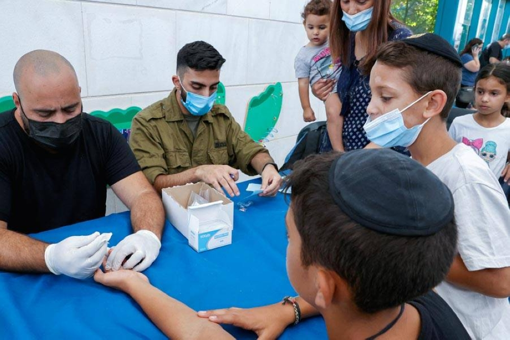 Israeli children undergo Covid-19 antibody testing in the coastal city of Netanya on August 22, 2021, before the start of the new school year. Israel launched antibody testing for children aged as young as three, seeking information on the number of unvaccinated youths who have developed protection against coronavirus ahead of the new school year, in order to avoid the hardships and developmental setbacks caused by school closures. AFP PHOTO