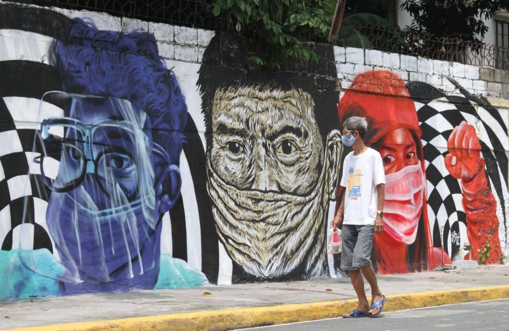 A man walks past a mural promoting the wearing of face mask on a street in Singalong, Manila on Monday, September 6, 2021. PHOTO BY RENE H. DILAN
