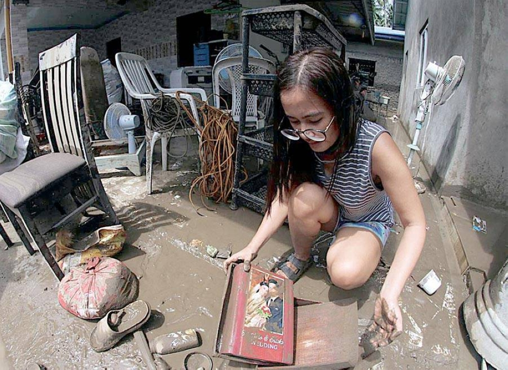 MAJOR CLEANUP A resident of San Isidro in Batangas City looks at her flood-damaged wedding album on Sept. 9, 2021, a day after Tropical Cyclone Jolina drenched the city. PHOTO BY RENE H. DILAN