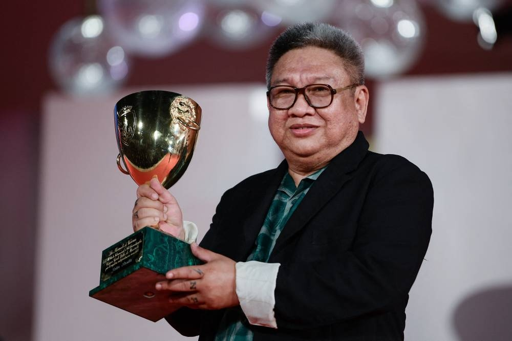 Filipino director Erik Matti poses with the trophy he received on behalf of actor John Arcilla, the Coppa Volpi for Best Actor in