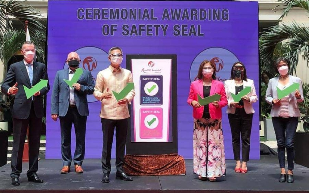 The ceremonial presentation of the Safety Seal is led by Resorts World Manila (RWM) President and Chief Executive Officer Kingson Sian and Pasay City Mayor Emi Calixto-Rubiano (center). Also present are (from left) Stephen Reilly, chief operating officer, RWM; Graham Coates, head, Megaworld Lifesyle Malls; Michelle Talavera-Pardo, officer-in-charge, Pasay City Business Permits and Licensing Office; and Gloria Aguhar, director, Pasay City Department of the Interior and Local Government. CONTRIBUTED PHOTO