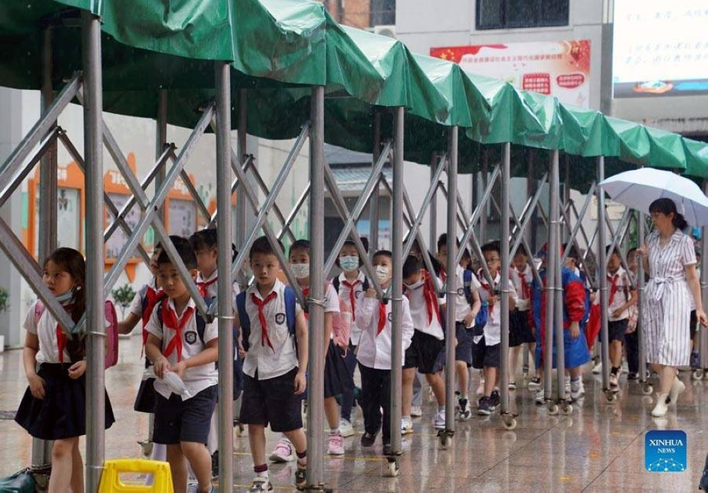 Students line up under the shelter of a removable awning after class at a primary school in Huangpu District, east China's Shanghai, Sept. 13, 2021. XINHUA PHOTO