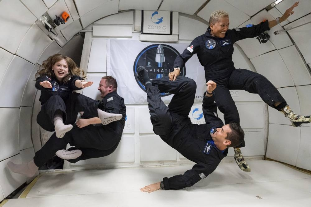 In this July 11, 2021 photo provided by John Kraus (from left) Hayley Arceneaux, Chris Sembroski, Jared Isaacman and Sian Proctor float during a zero gravity flight out of Las Vegas. The plane, a modified Boeing 727, flies multiple parabolic arcs to provide 20-30 seconds of weightlessness. PHOTO BY JOHN KRAUS/ INSPIRATION4 VIA AP