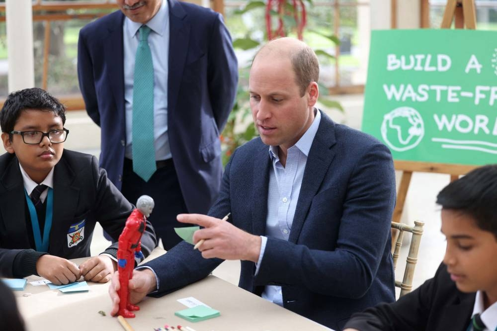Britain's Prince William, Duke of Cambridge interacts with children from The Heathlands School, Hounslow during a visit to take part in a Generation Earthshot educational initiative comprising of activities designed to generate ideas to repair the planet and spark enthusiasm for the natural world, at Kew Gardens, London on October 13, 2021. AFP PHOTO